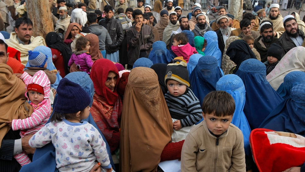 Crowded group of people in Afghanistan looking expectantly. Small children staring at the photographer.
